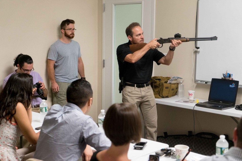 "Chad Nye, an associate professor of journalism at Keene State, demonstrates a long rifle during the CTSPJ-sponsored event ""Journalism on Target"" held at Greyson Guns in Orange, Conn. Aug. 22. 